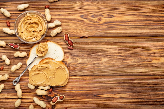 Тост бутерброд с арахисовым маслом. ложка и банку арахисового масла и арахиса для приготовления завтрака на коричневой деревянной предпосылке. сливочно-арахисовая паста плоская планировка с местом для текста.