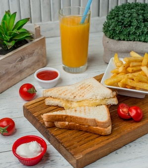 Toast sanwdiches with cheese inside with fries, tomato sauce and glass of orange juice.
