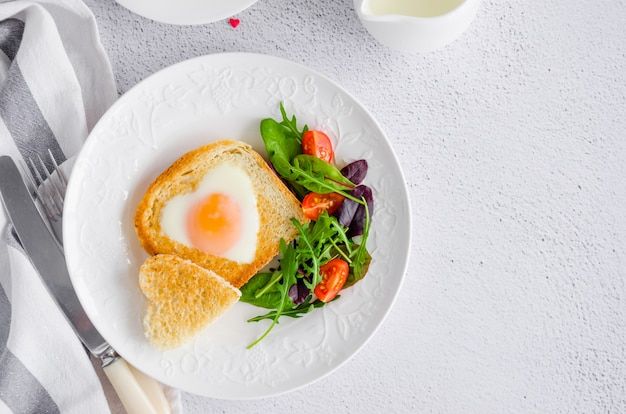 Toast in shape of heart with egg on a white plate with arugula and cherry tomatoes
