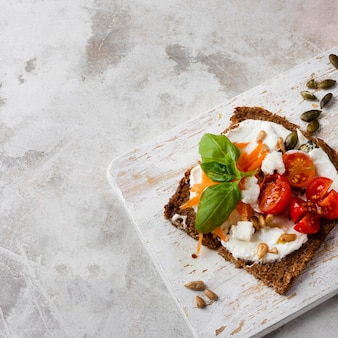 Toast slice with cherry tomatoes on marble high view