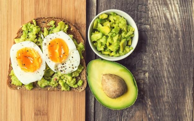 소박한 나무 배경에 아보카도와 달걀을 곁들인 토스트