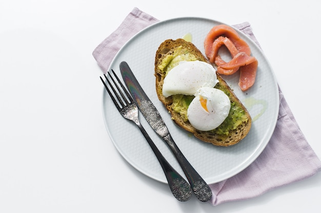 Toast with avocado, egg, salmon and black bread.