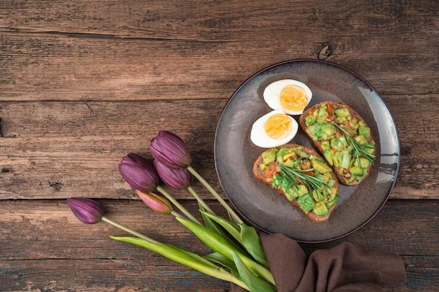 Тост с авокадо, яйцами и тюльпанами на деревянном фоне.