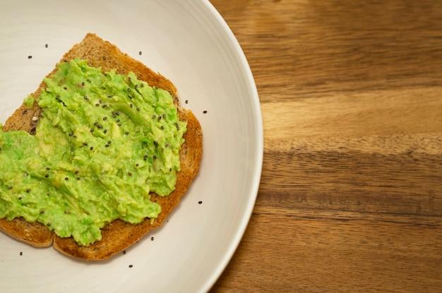 Тост с авокадо на белой тарелке с деревянным фоном. концепция здорового питания, диета, вегетарианская пища, вегетарианская вегетарианская пища.