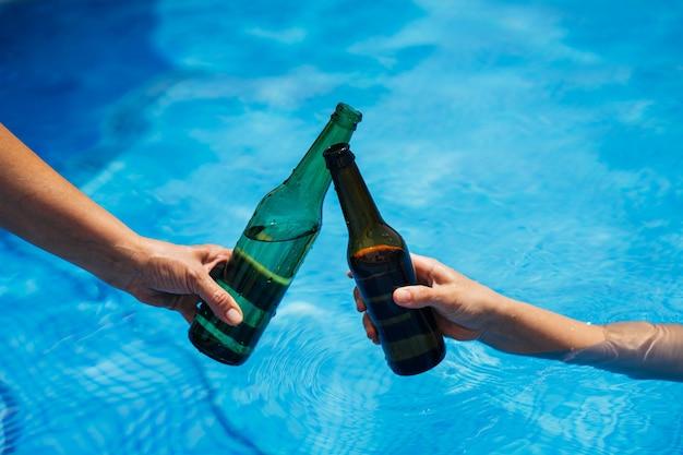 여름 휴가 기간 동안 수영장 위에 맥주 병으로 건배.