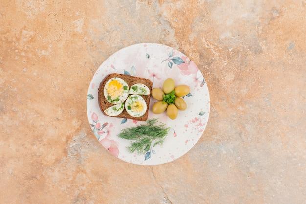 ゆで卵のトースト、白い皿にオリーブ