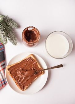 Toast with chocolate cream butter, jar of chocolate cream and pine branch