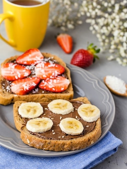 Toast with chocolate and fruits on a gray plate. strawberries and bananas on stone kitchen table