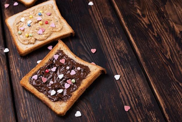 ダークウッドの背景にカラフルなハートをまぶしたチョコレートペーストとピーナッツバターのトースト、甘いデザート。