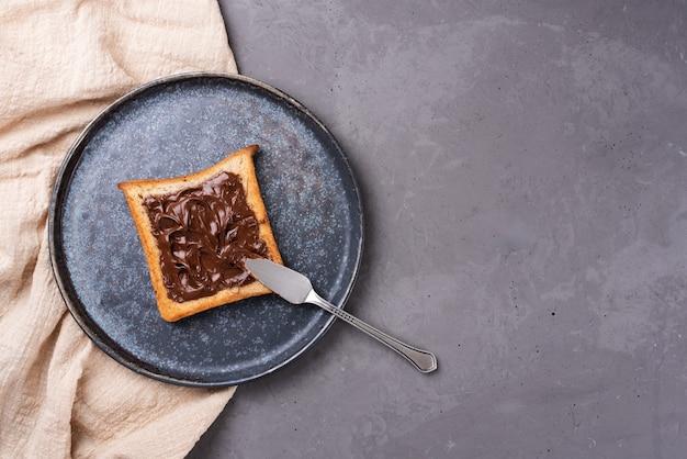 テキスタイルと灰色のコンクリートの背景のプレートにチョコレートペーストで乾杯します。