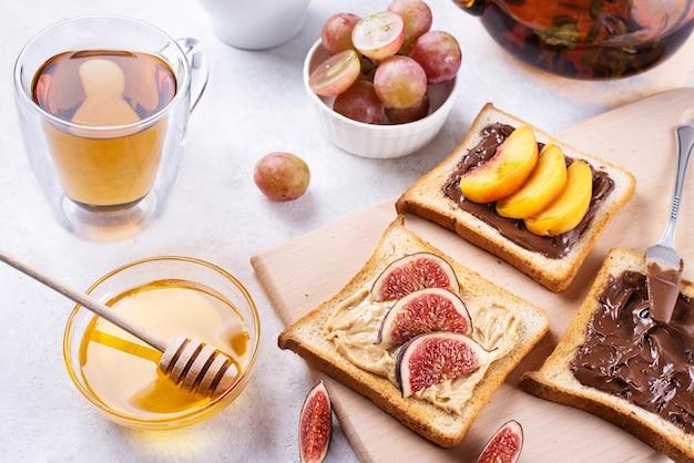 チョコレートスプレッド、ピーナッツバターピーチ、イチジクを白いテーブルに載せたトーストを朝食に、ヘルシーなデザートとしてお召し上がりいただけます。