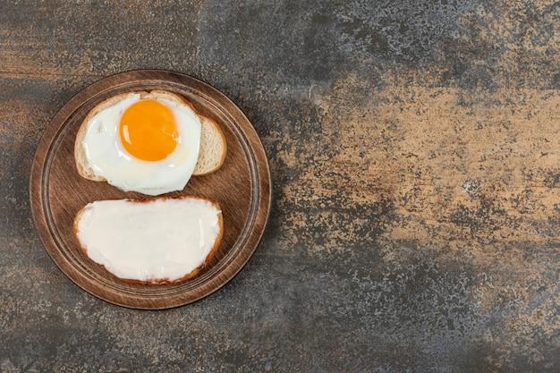 Toast con crema di formaggio e uova su tavola di legno.