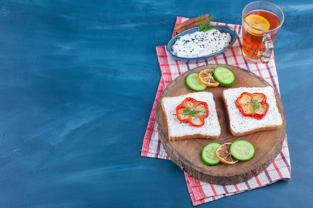 Toast with cream and sliced peppers on wood piece and glass of tea.