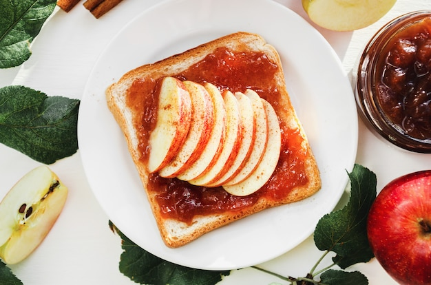 Toast with a crushed apple jam, slices of fresh apples, cinnamon on a plate on a white table.