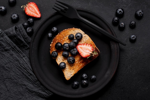 Toast with delicious slices of fresh strawberries and blueberries