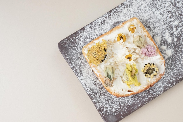 Toast with dried flowers and flour on dark cutting board .
