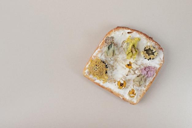 Pane tostato con fiori secchi e farina sulla tavola grigia.