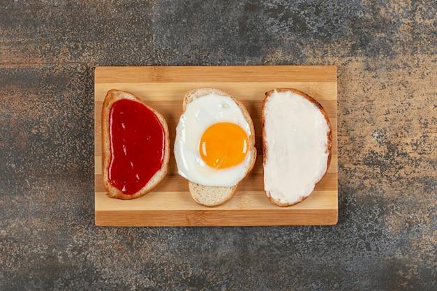 Toast con uova, crema di formaggio e marmellata su tavola di legno.