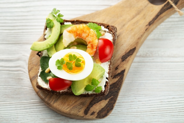 Toast with egg, shrimp, avocado, cheese, parsley and pine nuts