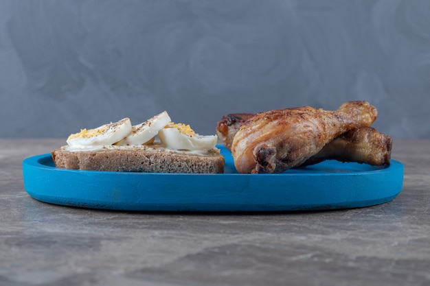 Toast con uova e cosce di pollo sul piatto blu.