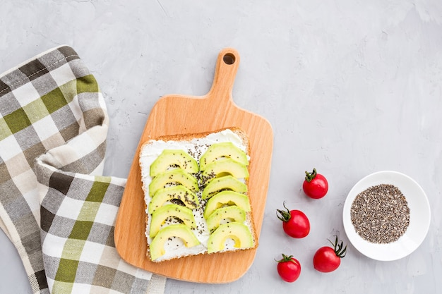 Toast with fresh avocado, cream cheese and chia seeds on gray concrete