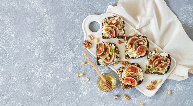 Toast with fresh figs, ricotta, nuts and honey on stone table, flat lay and copy space