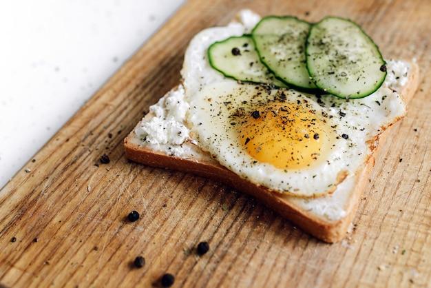 Тост с жареным яйцом и свежим огурцом на деревянной подставке вкусный быстрый завтрак