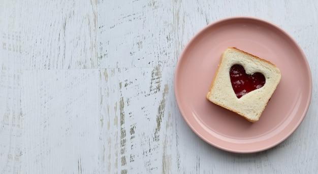 Тост с сердцевидным джемом на розовой тарелке, деревянный белый стол