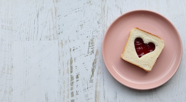 Toast with heart-shaped jam on a pink plate, wooden white table flat lay