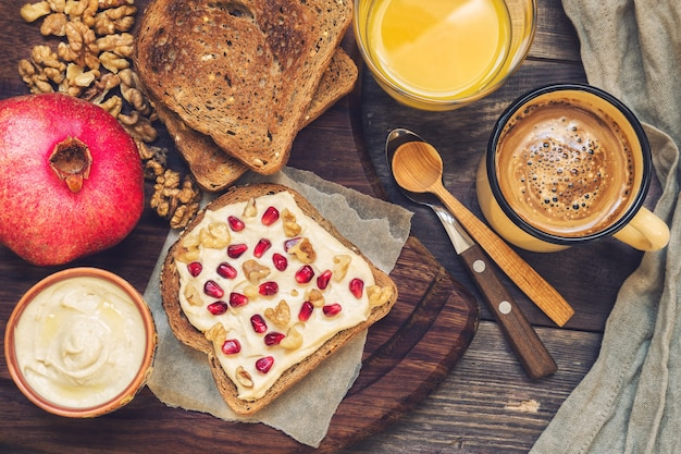 Toast with hummus, wallnuts and pomegranate on rustic wooden. healthy breakfast.