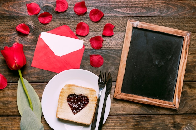 Toast with jam and cutlery on plate near flower, petals, letter and photo frame