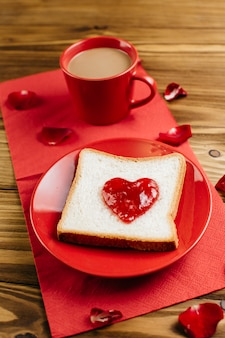 Toast with jam in heart shape on plate