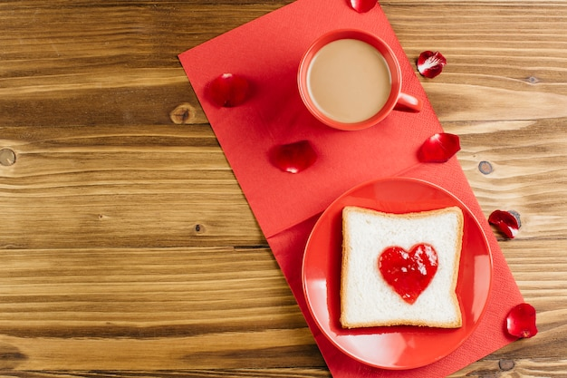 Toast with jam in heart shape on red plate