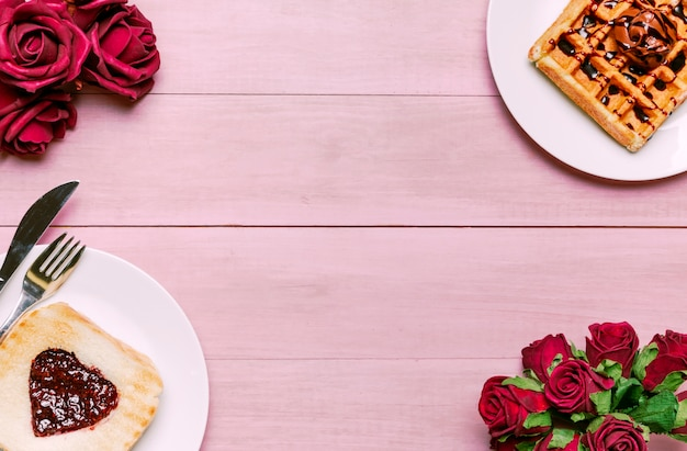 Toast with jam in heart shape with belgian waffle and roses