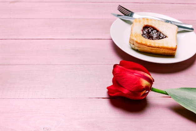 Toast with jam in heart shape with red tulip