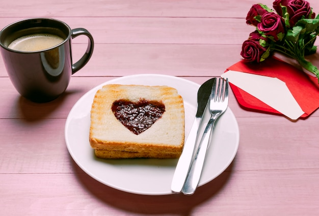 Toast with jam in heart shape with roses and coffee