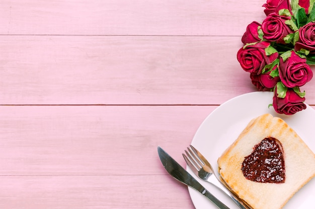 Toast with jam in heart shape with roses