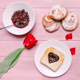 Toast with jam in heart shape with tulip and berries