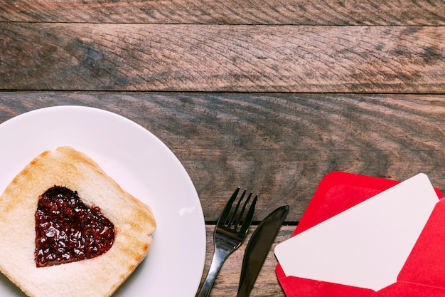 封筒とカトラリーの近くの皿にジャム付きトースト