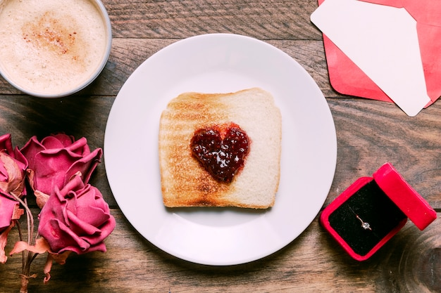 Toast with jam on plate near cup of drink, flowers, envelope and ring in gift box
