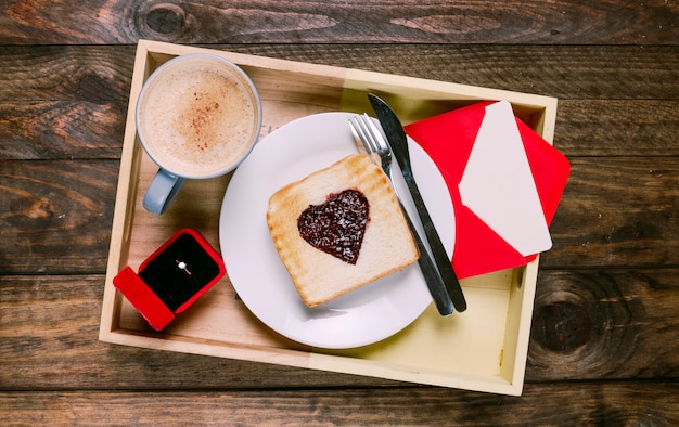 Toast with jam on plate near cutlery, cup of drink, envelope and ring in gift box on board