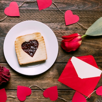 Toast with jam on plate near flower, letter and ornament hearts