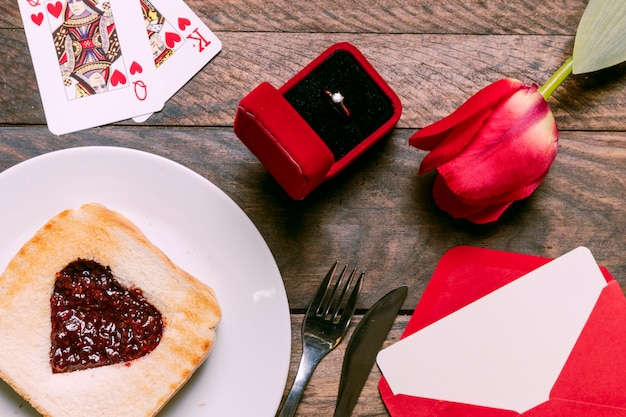 Toast with jam on plate near playing cards, flower, envelope and ring in gift box