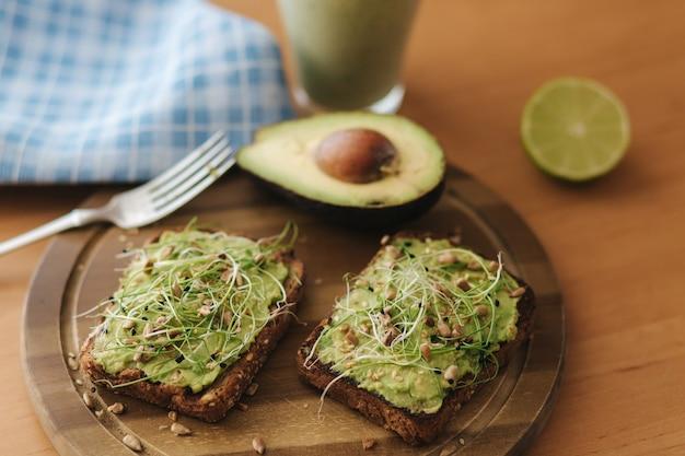 Тост с микрозеленью и гуакамоле сверху. ржаной тост на деревянной доске. здоровое питание дома. концепция веганской еды.