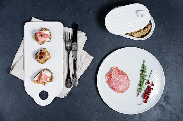 Тост с пармой, салями и гусиным паштетом на белой разделочной доске