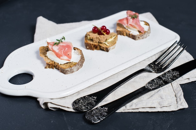 Toast with parma, salami and goose pate on a white chopping board