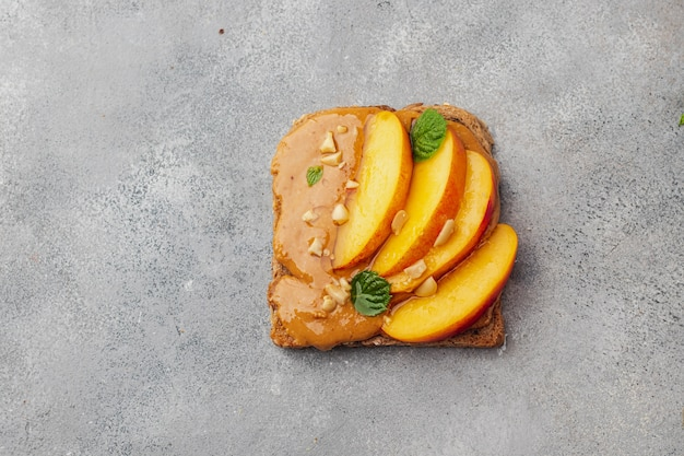 Toast with peanut butter, honey, mint, peanut and nectarine. flatlay with copyspace