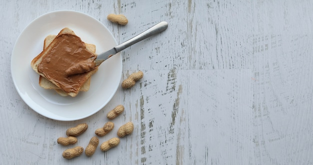 Toast with peanut paste on a white surface, flat lay copyspace