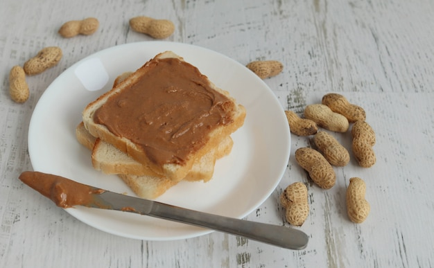 Toast with peanut paste on a white surface