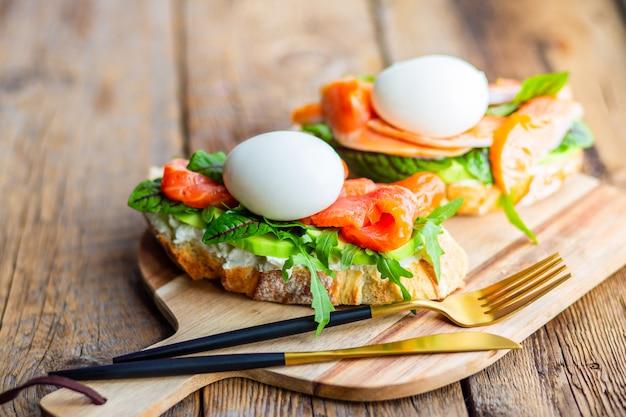 ポーチドエッグ、アボカド、ルッコラ、チーズ、赤い魚とハーブのトースト。おいしいランチ。健康的な脂肪と適切な栄養。アボカドのおいしいトースト。トーストにポーチドエッグが広がる